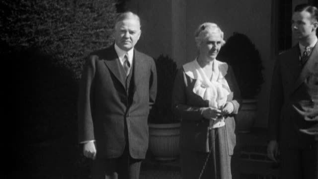 Herbert Hoover talks to a crowd of people milling about / stands in front of doorway to house with dogs and former first lady Lou Hoover / smile and...