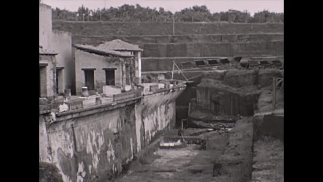 vídeos y material grabado en eventos de stock de herculaneum italy in 1933 / entering the harbour passenger vessel travels across the frame / view of electric train with carriages in town / view of... - excavar