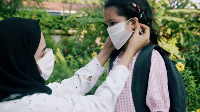 here, put your mask on before going to school, it will protect you from virus. - school uniform stock videos & royalty-free footage