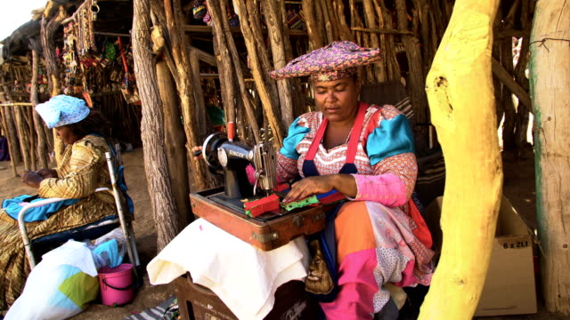 stockvideo's en b-roll-footage met herero tribe- women sewing in the street, dressed in traditional clothes - namibië