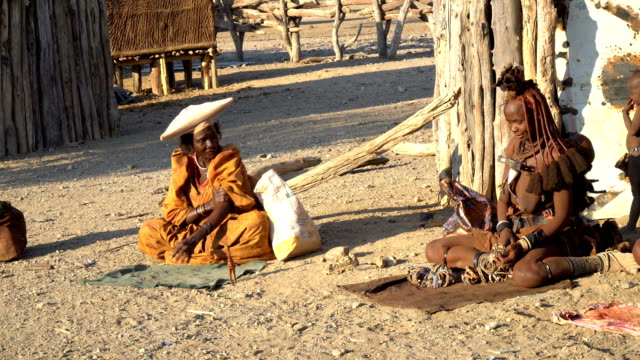 Herero woman and Himba woman selling crafts in the village market