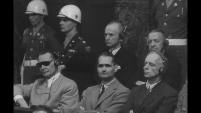 hermann goering in the dock seated next to rudolf hess and joachim von ribbentrop karl doenitz erich raeder behind them / vs high angle view of the... - processi di norimberga video stock e b–roll