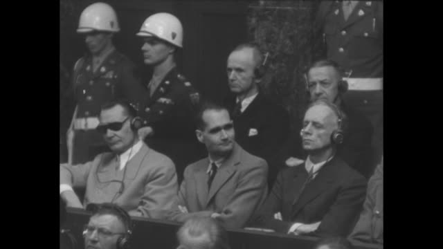 hermann goering sitting in prisoner's dock with hand over forehead rudolf hess sitting next to him looking at camera / defendants sitting in dock in... - hermann goering stock videos and b-roll footage