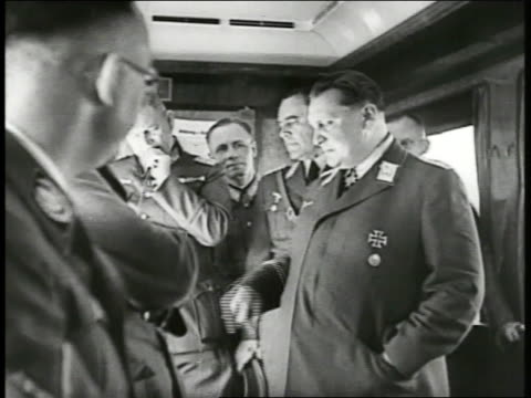 hermann goring stands gesturing at map on table w/ other officers goring pointing at map heinrich himmler fg pan to hitler seated in chair ms goering... - adolf hitler stock-videos und b-roll-filmmaterial
