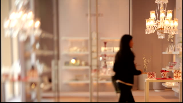 hermes boutique. rack-focus on a woman customer as she walks past a display in the hermes boutique in doha. the boutique is full of luxurious items. - crystal stock videos & royalty-free footage