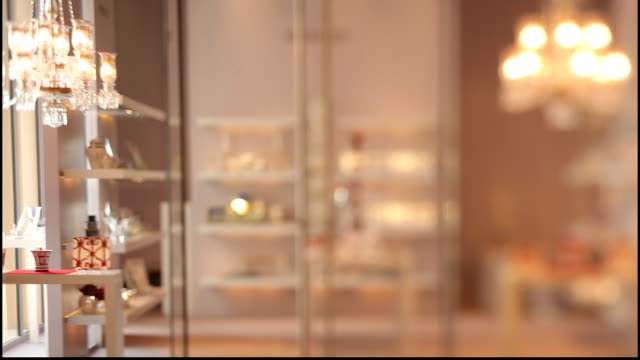 hermes boutique. view of a couple walking past a display in the hermes boutique in doha. the boutique is full of luxurious items. - crystal stock videos & royalty-free footage