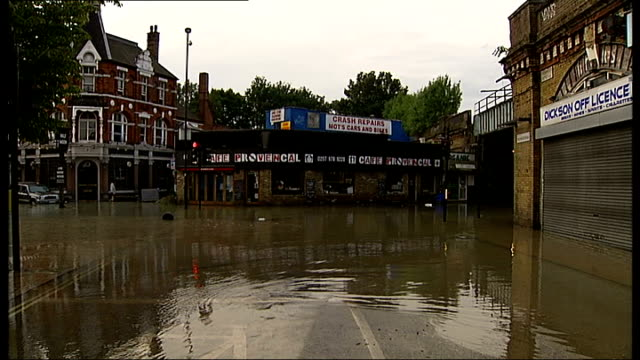 herne hill flooding caused by burst water main england london herne hill ext water gushing into drain flooded road pan firefighters pumping water... - herne hill stock videos & royalty-free footage