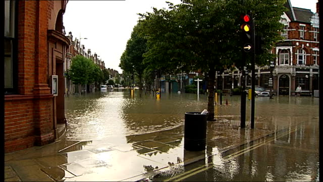 herne hill flooding caused by burst water main england london herne hill ext water gushing into drain flooded road pan people wading through flood... - herne hill stock videos & royalty-free footage
