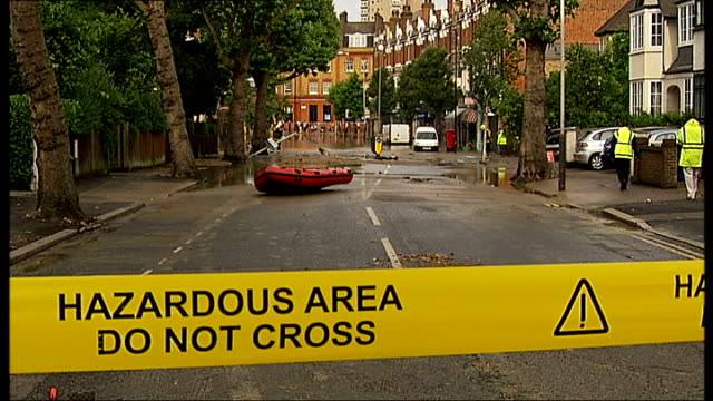 Herne Hill flooding caused by burst water main Fire officers with fire engines behinf cordon tape talking to members of public / Uprooted road sign /...