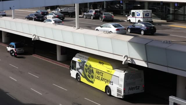 Hertz Global Holdings Inc and Avis Budget Group Inc shuttle buses drive through Los Angeles International Airport in Los Angeles California US on...