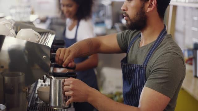 vídeos de stock, filmes e b-roll de ele é um artista atrás da cafeteira - barista