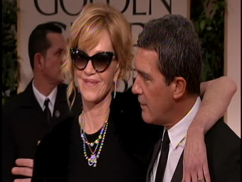 vídeos de stock e filmes b-roll de he's wearing a black tux with a tie and she is wearing a black gown and sunglasses - melanie griffith