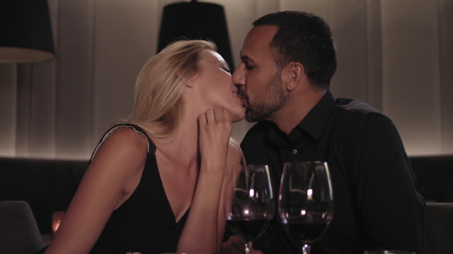 heterosexual couple dating, talking and flirting while having dinner and red wine in a hotel restaurant - blonde woman with long hair and tanned man with short dark hair and trimmed beard, both in their 30s. he wears a black shirt, she a black dress. - zungenkuss stock-videos und b-roll-filmmaterial