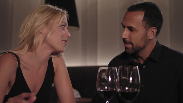 heterosexual couple dating, talking and flirting while having dinner and red wine in a hotel restaurant - blonde woman with long hair and tanned man with short dark hair and trimmed beard, both in their 30s. he wears a black shirt, she a black dress. - black dress stock videos & royalty-free footage