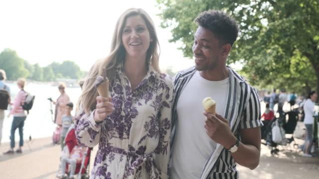 heterosexuelles paar isst eis in einem park in london - tourist stock-videos und b-roll-filmmaterial