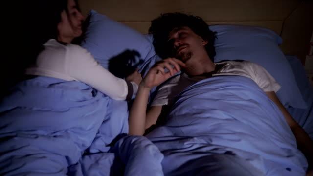 ベッドで異性愛者のカップルは、男は眠り、口を開けていびきをかきますが、疲れた女性は枕を頭に抱えてベッドに座っていびきをかいていらいらします。 - 無呼吸点の映像素材/bロール