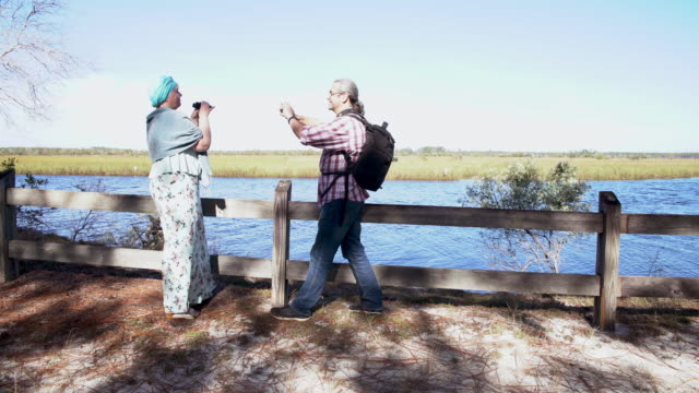 a heterosexual couple, man and woman, watching birds with a binocular in the ochlockonee river state park, north florida. the man taking a picture of the woman with a smartphone. - osservare gli uccelli video stock e b–roll