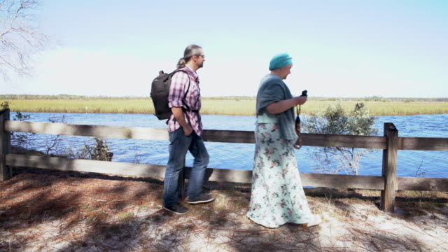a heterosexual couple, man and woman, watching birds with a binocular, then they walking out. ochlockonee river state park, north florida. - bird watching stock videos & royalty-free footage