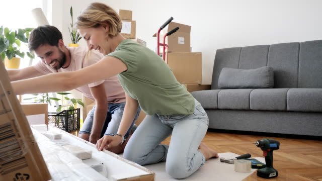 heterosexual couple moving in new apartment and assembling furniture. couple sitting on the floor and unboxing flat pack furniture - ethnicity stock videos & royalty-free footage
