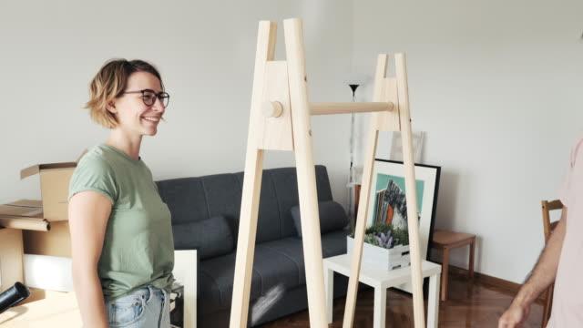 vidéos et rushes de couples hétérosexuels se déplaçant dans le nouvel appartement et assemblant des meubles. couples s'asseyant sur le plancher et affichant le manuel de lecture comment assembler l'étagère - bricolage
