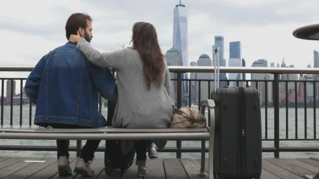 異性のカップルの方のベンチに座って、ニューヨーク市で待っています。