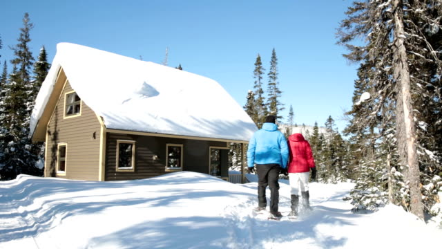 heterosexual couple walking with snowshoes - chalet stock videos & royalty-free footage