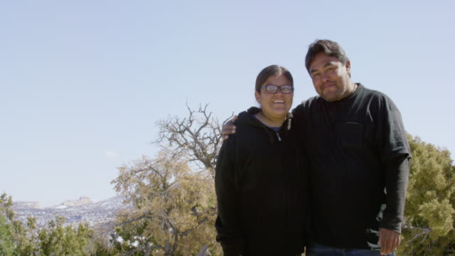 a heterosexual native american couple in their thirties hugging, smiling, and laughing at each other and at the camera on a sunny day outdoors in utah - north american tribal culture stock videos & royalty-free footage