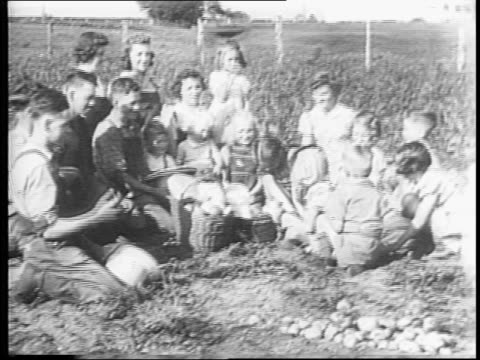 l'heureux family / family sits down in their field for a picnic lunch / family prays / group around basket / girl takes out apple / another girl... - picnic basket stock videos and b-roll footage