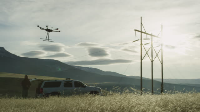 a hexacopter drone lifts up into the air in a grassy field while a pilot/operator watches next to an suv and some power lines on a partly cloudy day outdoors - propeller stock videos & royalty-free footage