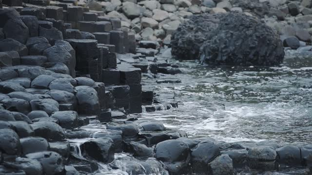 hexagon geological formations of giant causeway coastline, northern ireland, at dusk - boulder rock stock videos & royalty-free footage
