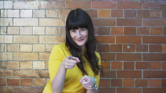 """hey!"" woman does playful point and wink. - bangs stock videos and b-roll footage"