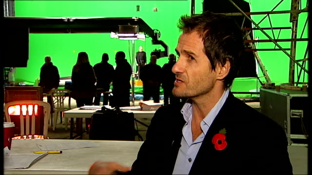 heyman chatting to reporter david heyman interview sot cutaway actor standing in front of green screen london: tracking shot along corridor in double... - film negative stock videos & royalty-free footage