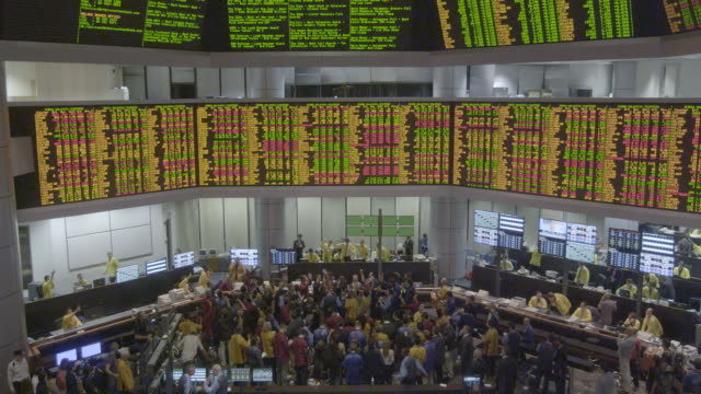 ws hi angle down to int. mercantile trade exchange, malaysia, traders on floor waving hand signals, big boards above - market stock videos & royalty-free footage