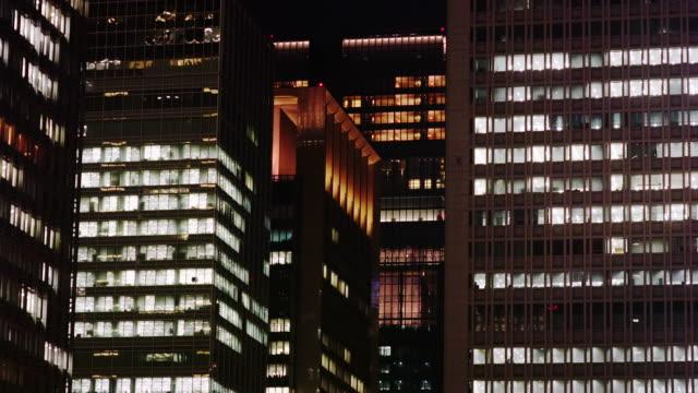 hi rise office buildings around tokyo station at night - オフィスビル点の映像素材/bロール