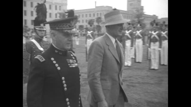 cu hibiscus abloom / officers and dignitary inspect vmi cadets on grounds in front of building / officers and dignitary walking on field marching... - ピンを刺す点の映像素材/bロール
