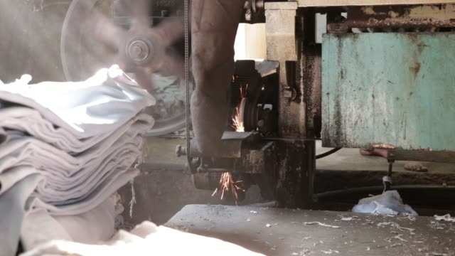 Hides sit in piles as employees work on a splitting machine at the Sheong Shi Tannery in Kolkata West Bengal India on Tuesday Dec 26 Sparks fly on...