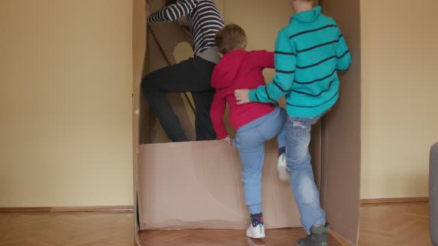 vidéos et rushes de se cachant dans une boîte en carton, poche tourné - activité physique