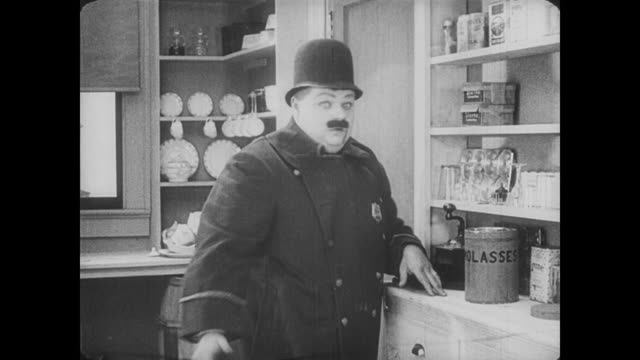 1917 Hiding man (Fatty Arbuckle) finds police officer's uniform in pantry and puts it on for a disguise