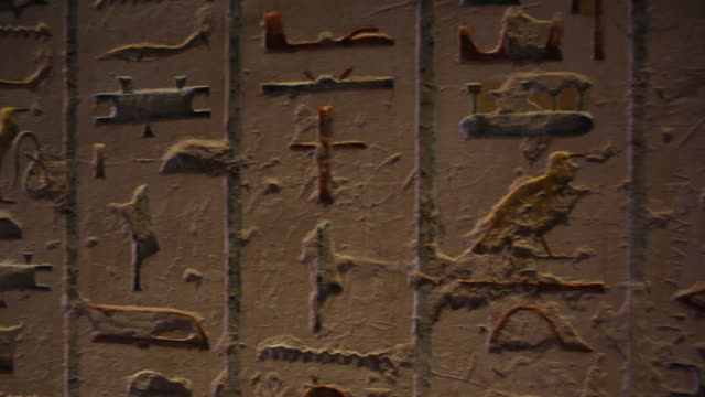 hieroglyphics inside an ancient egyptian tomb pan to young woman located in the 'valley of the kings' - valley of the kings stock videos & royalty-free footage