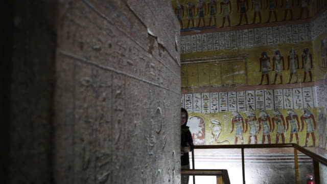 hieroglyphics inside an ancient egyptian tomb young woman walks in frame located in the 'valley of the kings' - gravvalv bildbanksvideor och videomaterial från bakom kulisserna