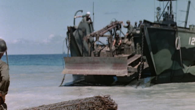 la higgins boat delivering bulldozer to beach of pacific island marines watching - landungsboot stock-videos und b-roll-filmmaterial
