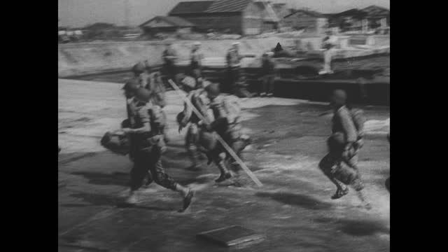 higgins boats speed thought the water and us marines wade ashore; the american flag is hoisted to the top of a tower with two platforms with a wind... - 戦後点の映像素材/bロール