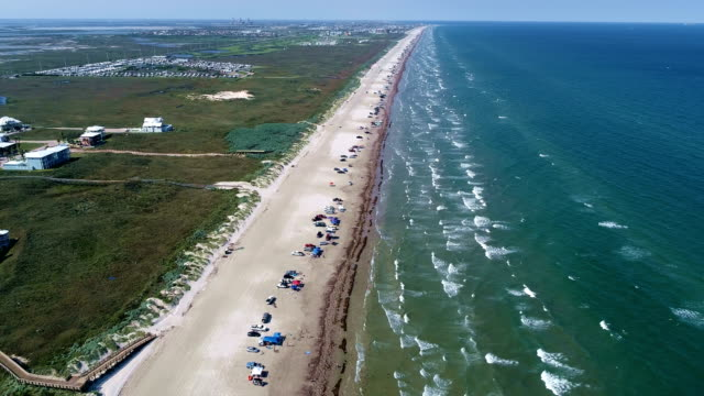 high above the waves crashing on beach with long perspective aerial drone view above padre island - gulf of mexico stock videos and b-roll footage