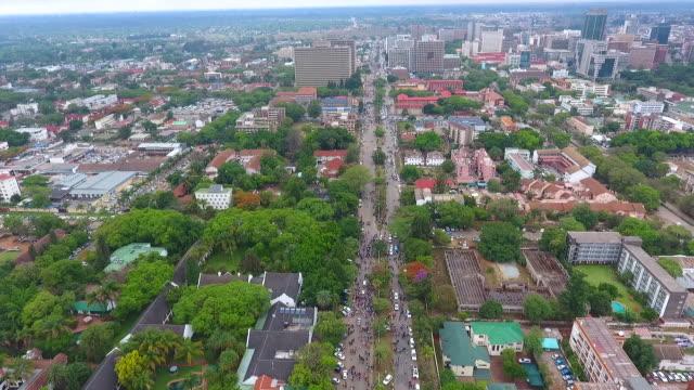 high aerial drone shot tracking simon muzenda st, harare towards high rise buildings during street celebrations following robert mugabe's resignation... - repubblica dello zimbabwe video stock e b–roll