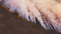 High aerial fly over view of a grass fire in the Okavango Delta, caused by drought and climate change, Botswana