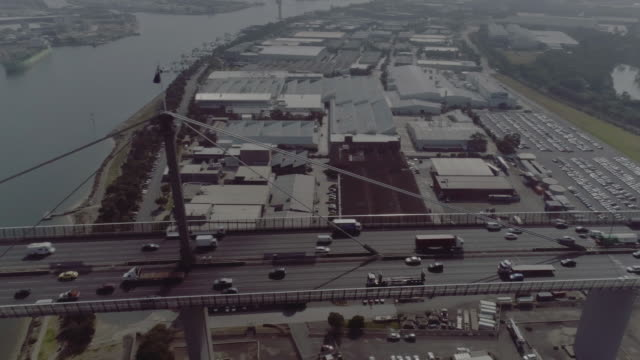 high aerial pan of melbourne's west gate bridge with australian flag. melbourne australia - cable box stock videos & royalty-free footage