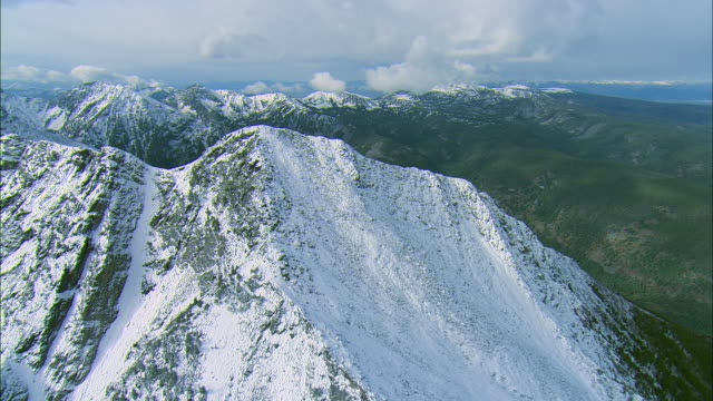 vidéos et rushes de high altitude flight across a snow-covered ridge in the spanish peaks mountain range near big sky, mt to reveal canyon below - montana