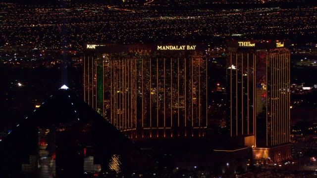 vídeos de stock e filmes b-roll de hd night aerial *high altitude xws mandalay bay thehotel reflective towers moving northeast to include luxor pyramid w/ light tip lights moving on... - pyramid