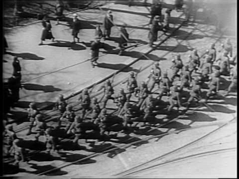 High angel shot of Nazi soldiers marching down a city street with civilians walking alongside on the sidewalk / medium long shot of Nazi soldiers...