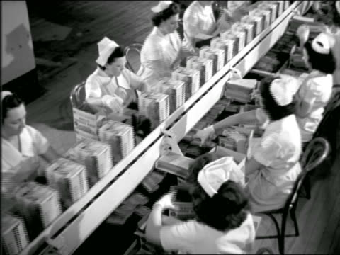 b/w high angle 1944 women with white caps packaging goods in boxes on conveyor belt in assembly line - occupazione industriale video stock e b–roll